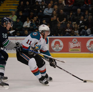 Geordie Wudrick muscles past defenseman Tanner Muth just before depositing his first of two goals against the Seattle T-Birds. (Photo: Wayne Moore - Castanet)