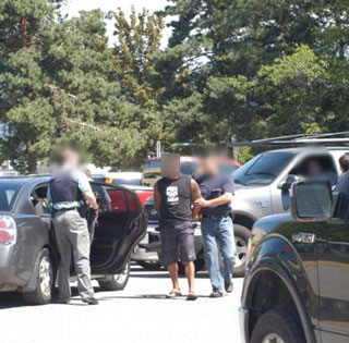 Joelon David Atish Verma (dressed in shorts) was arrested by RCMP Friday. (Photo: RCMP)
