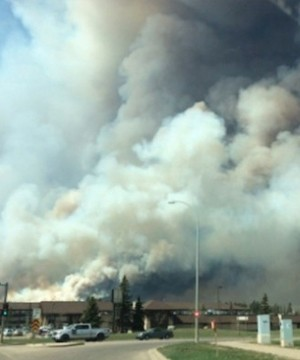 A thick cloud of acrid smoke hung over Fort McMurray as people who have fled the wildfire wondered about family, friends and their homes.