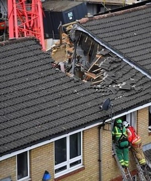 One dead as construction crane collapses onto homes in London.